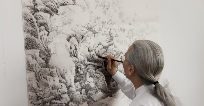 Liu dan painting a portion of a landscape, © Britta Erickson