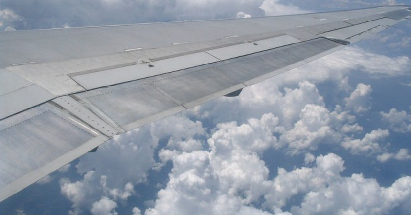 Airplane wing in front of cumulus clouds  | © Courtesy of D Coetzee/Flickr
