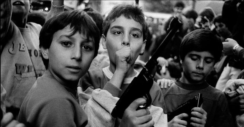 Festa del giorno dei morti. I bambini giocano con le armi Palermo – 1986, Courtesy Photo   Letizia Battaglia, MAXXI