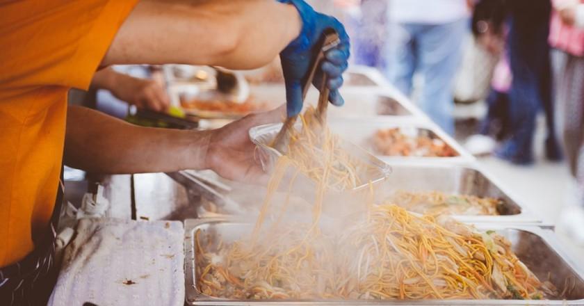 "<a href=""https://www.pexels.com/photo/person-in-orange-shirt-holding-aluminum-rectangular-container-104884/"">Preparing street food   Pexels</a>"