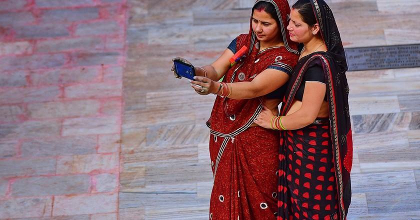 Indian women using cell phones.  ©Seree Tansrisawat / Shutterstock, Inc.