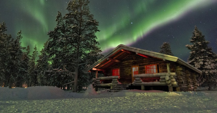 The northern lights above a wooden chalet  © Christ/ Flickr