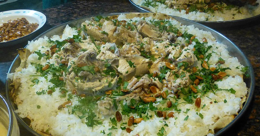 "<a href=""https://commons.wikimedia.org/wiki/File:Pr%C3%A9paration_du_mansaf-Jordanie_(8).jpg"" target=""_blank"">Jordanian Mansaf topped with herbs | © Ji-Elle / Wikimedia Commons</a>"