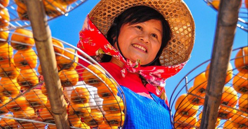 A Hakka woman in a traditional hat and scarf | Shutterstock