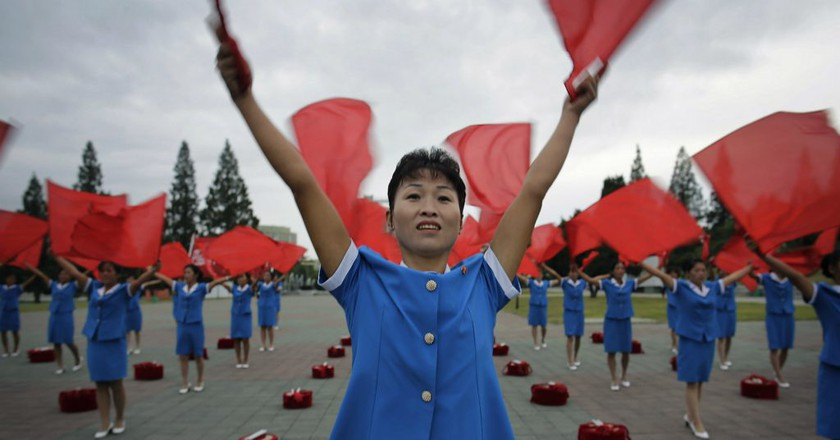 North Korean women wave flags cheering on their fellow countrymen as they start their day during morning rush hour in Pyongyang | © Wong Maye-E/AP/REX/Shutterstock