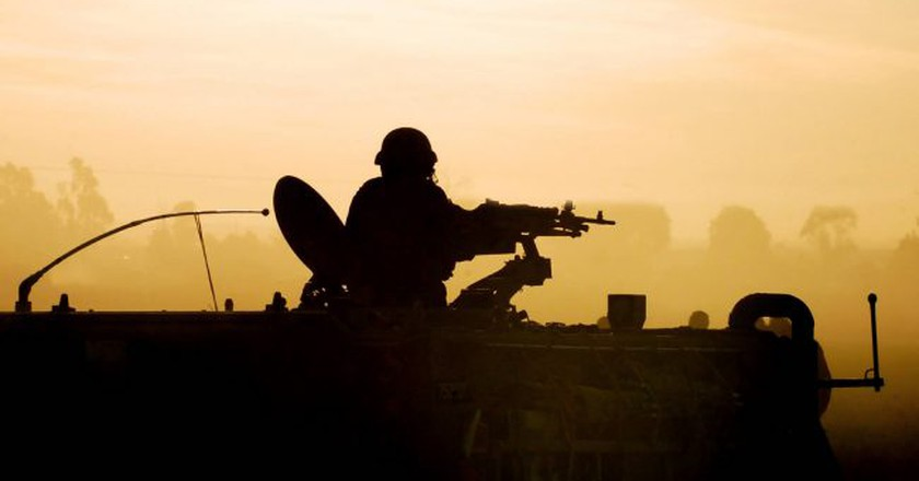 An army soldier preparing his tank and weapons at sunset | © ChameleonsEye/Shutterstock