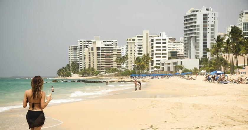 Woman walking on a beach in San Juan   © Andrew Hart/ Flickr