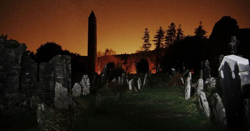 The round tower and graveyard at Glendalough at night, with the glow of Dublin to the north   © Rob Hurson / WikiCommons