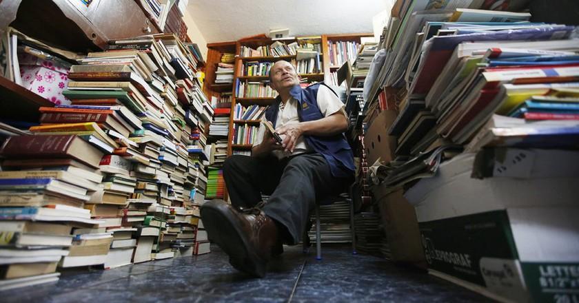 Jose Alberto Gutierrez sits among piles of books at his home in Bogota, Colombia | © Fernando Vergara/AP/REX/Shutterstock