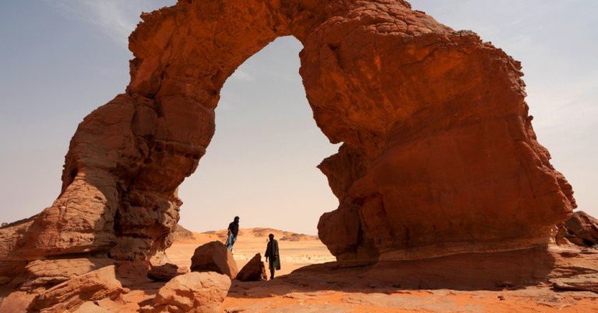 Tuaregs under a stone arch in the Tadrart Acacus in southwest Libya, part of a mountain range which stretches into Algeria | ©Sunsinger/Shutterstock
