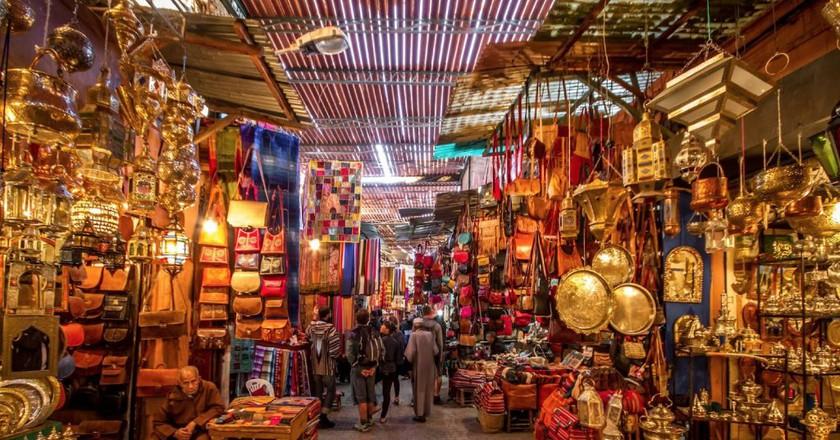 "<a href=""https://www.flickr.com/photos/nouamanb/34957182345/"" target=""_blank"">Wide array of goods in a Marrakech souk   © Nouaman Bentaj / Flickr</a>"
