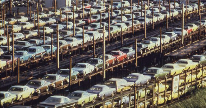 "<a href=""https://commons.wikimedia.org/wiki/File:FOB_DETROIT-NEW_CARS_ARE_LOADED_ONTO_RAILROAD_CARS_AT_LASHER_AND_I-75_-_NARA_-_549696.jpg"" target=""_blank"" rel=""noopener noreferrer"">New cars built in Detroit loaded for rail transport, 1973 