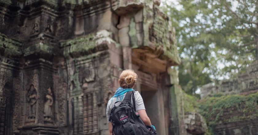"""<a href="""" https://www.pexels.com/photo/woman-wearing-black-hiking-backpack-standing-near-ancient-cave-during-daytime-198993/""""> Woman traveling 