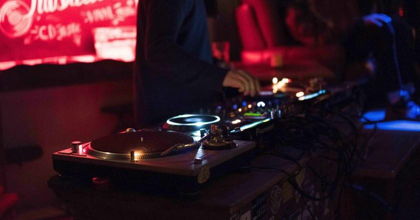"<a href = ""https://unsplash.com/search/nightclubs?photo=wMkqe4JCaAw""> Spin that record | © Modesta Žemgulytė/ Unsplash"