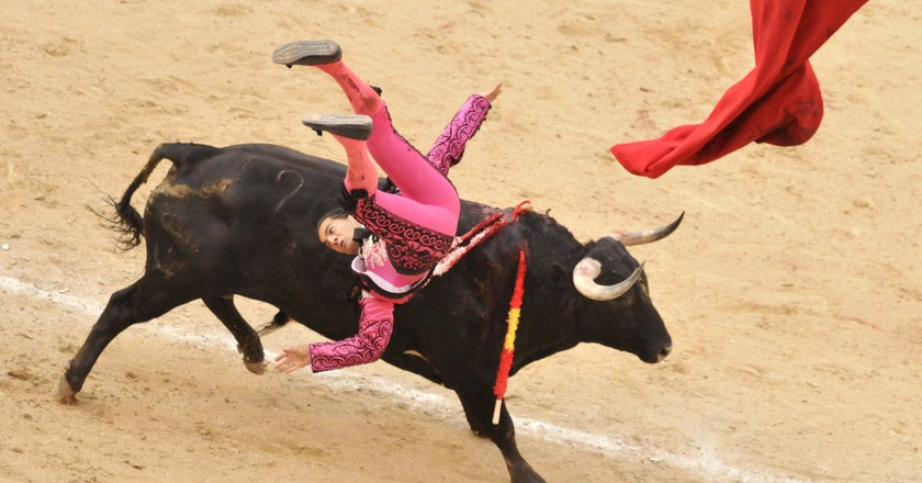 A bull tossed bullfighter (toreros) during a bullfight (Corrida) at a bullfight in Madrid.© Bumble Dee/Shutterstock