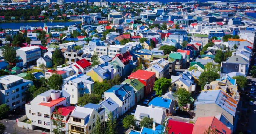 Beautiful super wide-angle aerial view of Reykjavik, Iceland with harbor and skyline mountains and scenery beyond the city, seen from the observation tower of hallgrimskirja | © Tsuguliev/Shutterstock