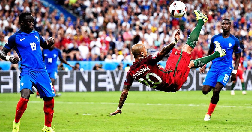 "<a href = ""https://commons.wikimedia.org/wiki/File%3ARicardo_Quaresma_performing_a_bicycle_kick_against_France_at_Euro_2016_final.jpg ""> Ricardo Quaresma performing a bicycle kick against France at Euro 2016 final │© www.dawn.com/Wikimedia Commons"