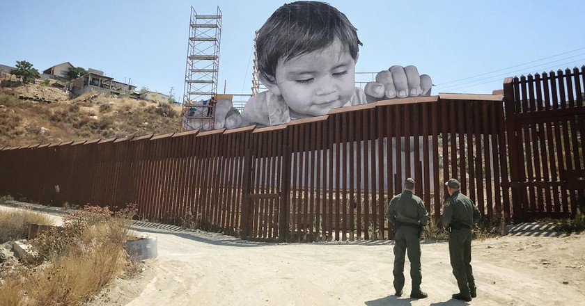 JR's portrait of Kikito peering over U.S. / Mexico border | © JR. Courtesy of Agence VU