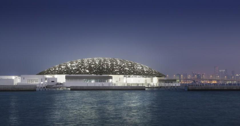 Louvre Abu Dhabi's exterior with Abu Dhabi's skyline (night) | © Louvre Abu Dhabi, Photography: Mohamed Somji