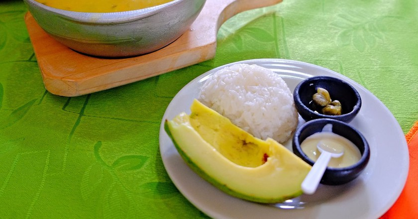 """<a href=""""https://www.flickr.com/photos/61266278@N00/25952438801"""" target=""""_blank"""" rel=""""noopener noreferrer"""">A full Colombian-style ajiaco with rice and avocado 
