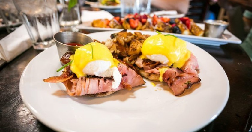 Blu Jam Benedict - Poached eggs on a toasted English muffin with Black Forest Ham, crispy bacon, topped with hollandaise sauce, served with potatoesΙ©City Foodsters/Flickr