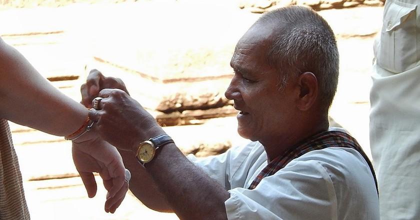 Monk ties thread around a tourist's wrist   © Michael Coghlan / Shutterstock