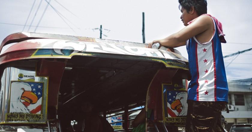 Man hanging on jeepney
