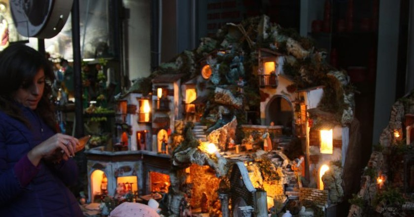 A child gazes at a nativity scene in San Gregorio Armeno Street.