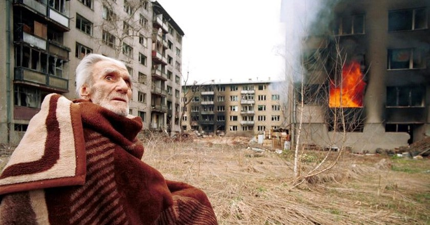 A Bosnian Croat man sits stunned and scared outside his burning home after rampaging Bosnian Serbs looted and set fire to his home in the final hours of siege on Mar 17, 1996 in Sarajevo, Bosnia   © Northfoto/Shutterstock