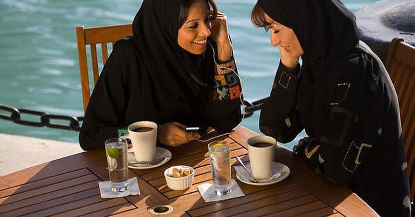 Women Listening to an MP3 Player Over Coffee  | © Peter Adams/Corbis