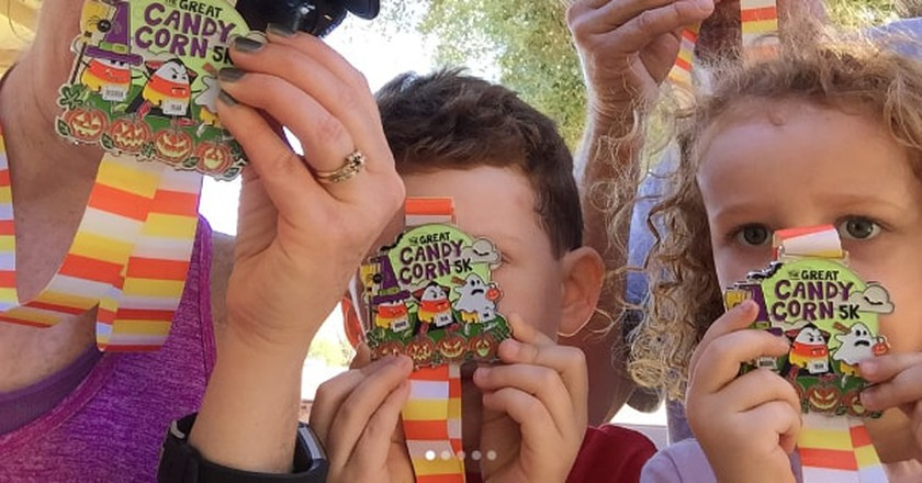Participants showcasing their Great Candy Corn 5K virtual race medals | © Gone For A Run