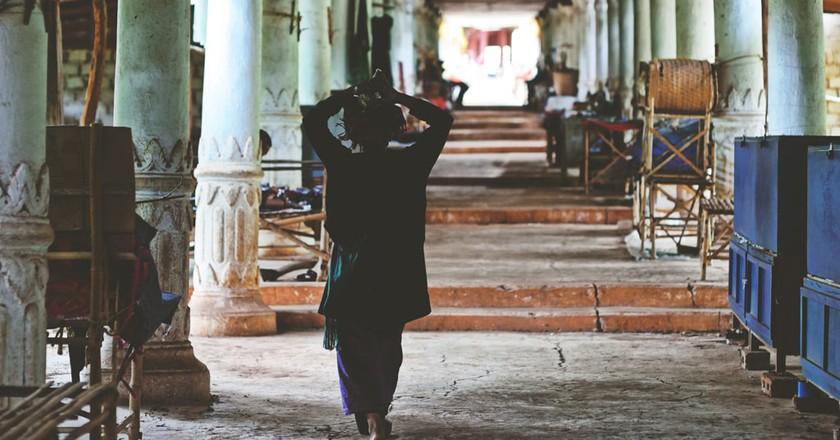 A Burmese woman walks through a market corridor at the Inn Dein Pagoda complex near Inle Lake, Myanmar  | © Chase Chisholm