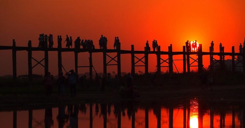 The sun sets vibrantly at U Bein Bridge near Amarapura, Myanmar | © momo / Flickr