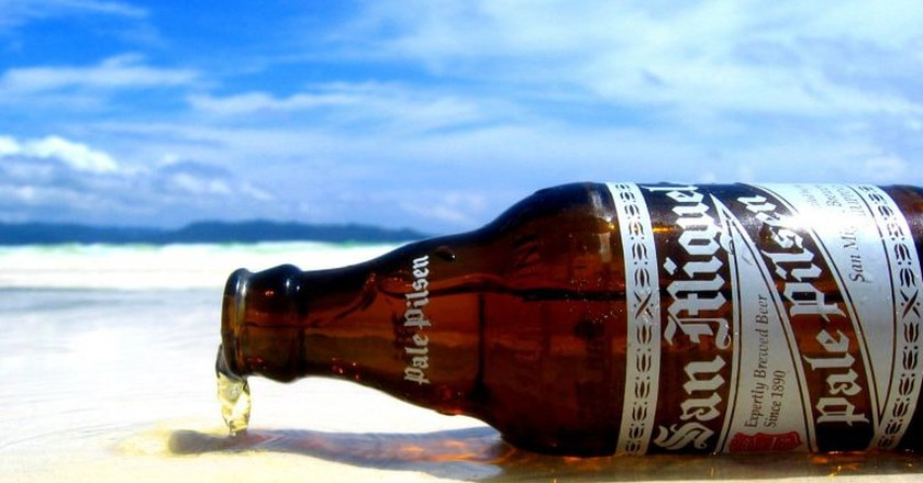 Bottle of San Miguel Pale Pilsen on the beach