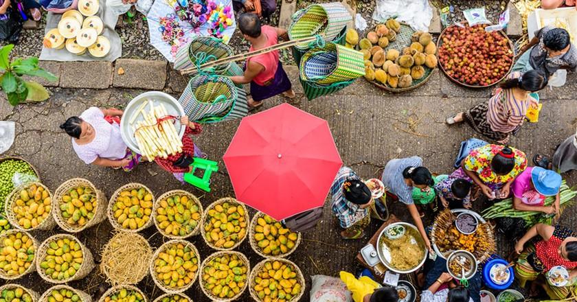 Market sellers and goers line the railway at Da Nyin Gone Market near Yangon, Myanmar    © Nguyen Quoc Ai / Shutterstock