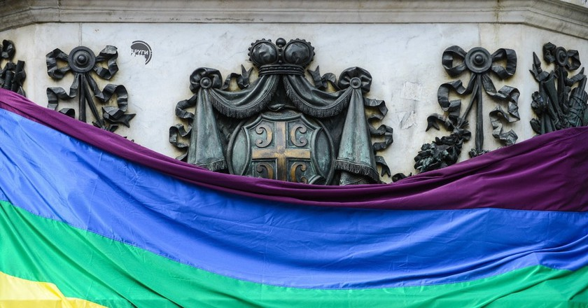 The Pride flag stands in front of the Serbian coat of arms | © Bobica10/shutterstock
