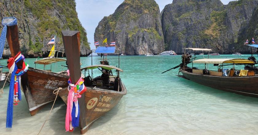 Thai long-tail boats, clear water, and limestone karsts at Maya Bay, Koh Phi Phi | © Kullez / Flickr