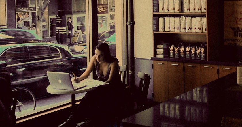 Girl writing in coffee shop.