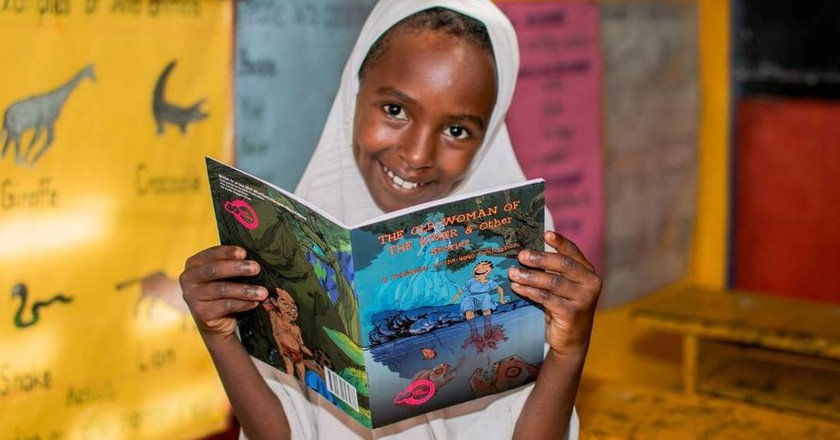 A Ugandan girl with a children's book written by Ugandan authors | © 40 Days Over 40 Smiles