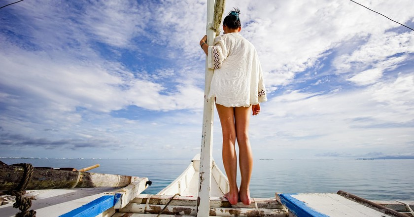 Woman standing on the bow of a bangka