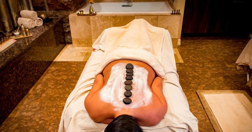A woman relaxes with a hot stone massage.