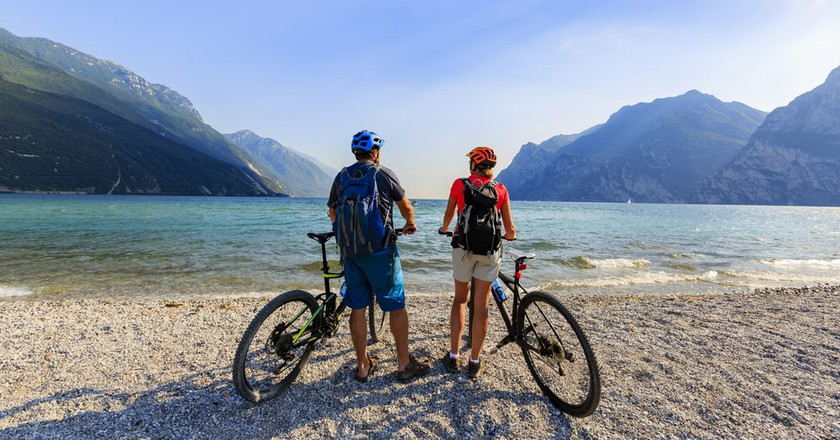 Cyclists take a break on a beach in Lake Garda | © gorillaimages / Shutterstock