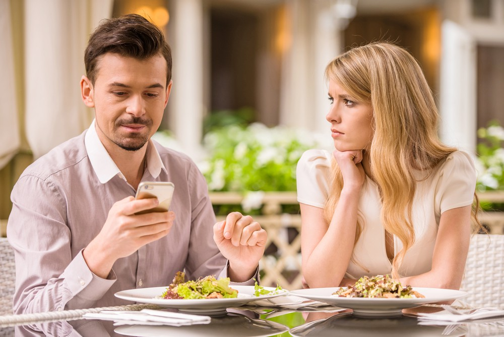 Couple in a restaurant with the man messing with he phone