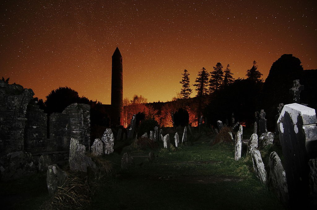The round tower and graveyard at Glendalough at night, with the glow of Dublin to the north | © Rob Hurson / WikiCommons
