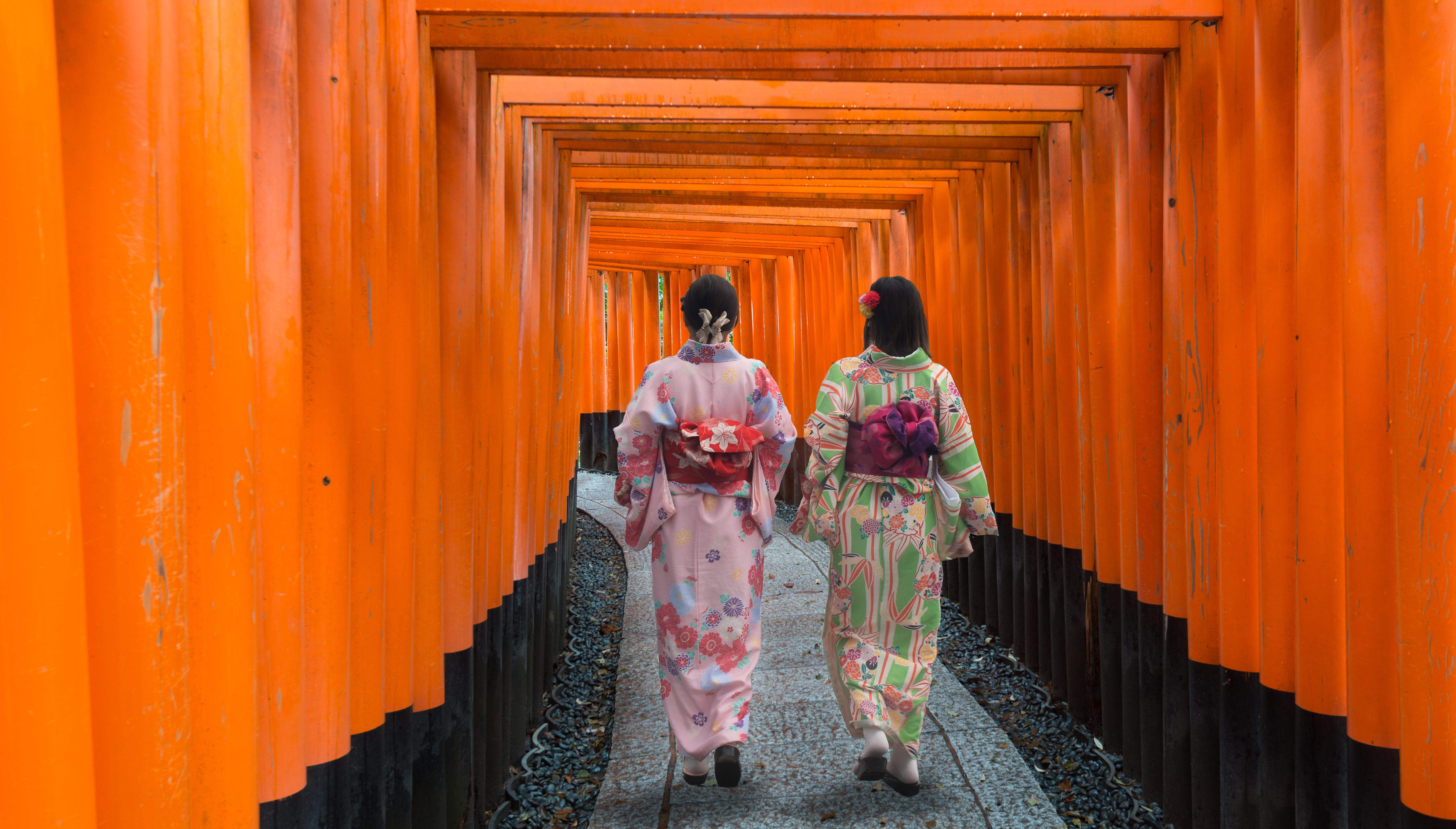 Two geishas among red wooden Tori Gate at Fushimi Inari Shrine in Kyoto, Japan.