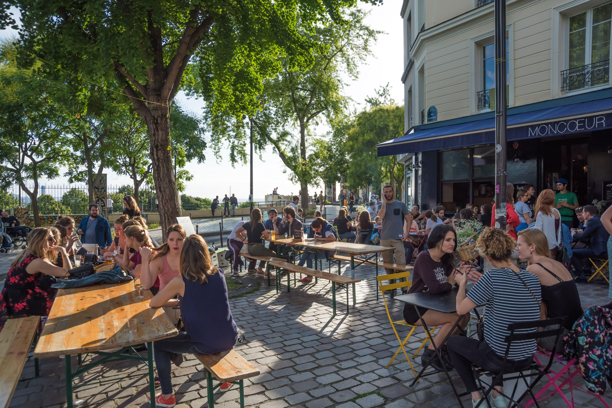 People enjoy drinks in the sun outside French restaurant Moncoeur Belleville in Paris